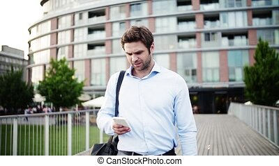 A young businessman with a smartphone walking in town, receiving bad news.