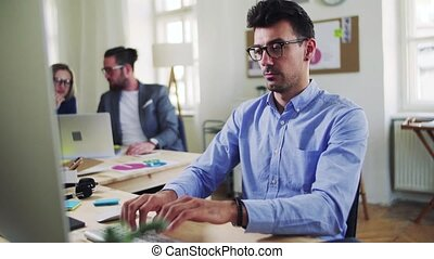 A young businessman with colleagues in a modern office,...