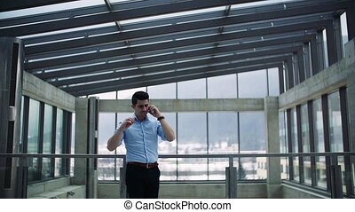 A young businessman with smartphone in corridor outside...