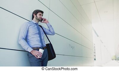 A young businessman with smartphone outside in a city,...