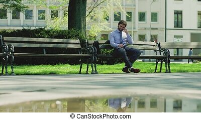 A young businessman with smartphone outside in city, sitting on bench, making phone call.