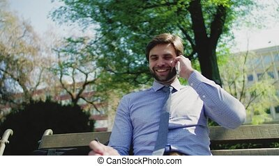 A young businessman with smartphone outside in city, sitting on bench, talking.