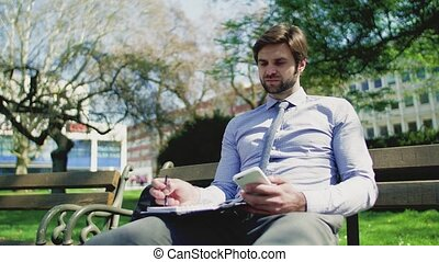 A young businessman with smartphone outside in city, sitting on bench, writing.