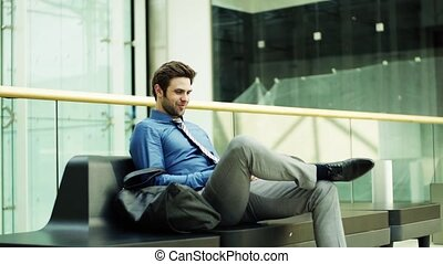 A young businessman with smartphone sitting on a bench in a modern building.