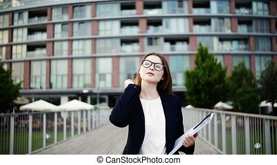 A young businesswoman with glasses walking on the bridge in a city.