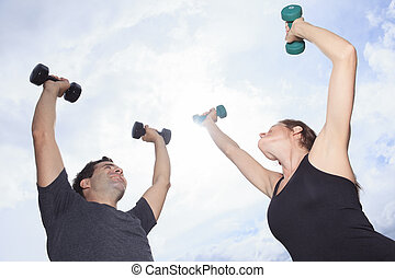 A Young, caucasian couple working out with dumbbells outside