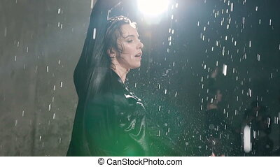A young Caucasian girl performs a modern dance barefoot in the water under the rain drops at studio. Emotional dance. Wet ballerina dancing at the water rain in indoors with the studio light