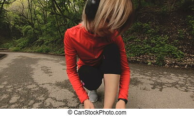 A young Caucasian girl sitting binds her shoelaces before...