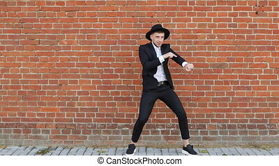 A young caucasian man in a black suit and hat is dancing and...