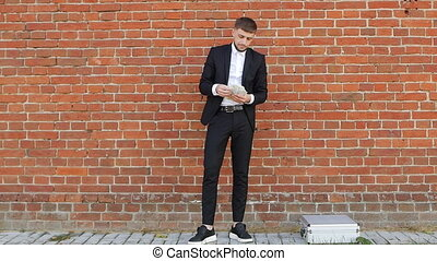 A young caucasian man in a black suit counts money against...