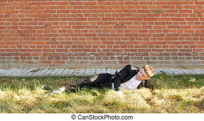 A young caucasian man in a black suit falls on the grass...