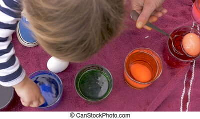 A young child helps her mother coloring easter eggs for the...