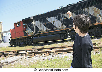 A young child posing at the railroad