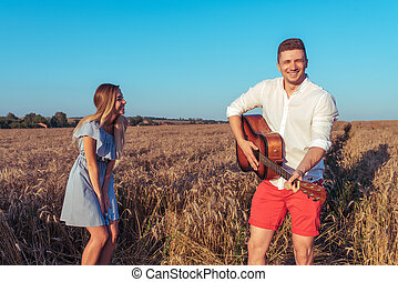 A young couple, a man and a woman in the summer in a wheat field, playing the guitar, laughing, smiling, relaxing in the fresh air. The concept of love is joy and fun in relationships.