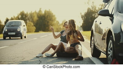 A young couple are hitchhiking standing on the road. A man...