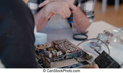 A young couple at repair cafe repairing household electrical devices.