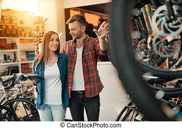 A young couple came to the bicycle shop to choose a new bicycle.