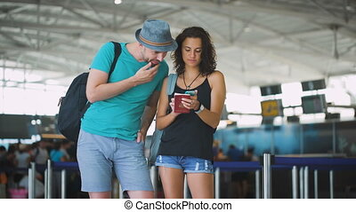 A young couple choosing a hotel at the airport