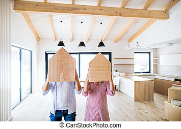 A young couple covering faces with wooden house. A moving in new home.