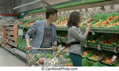 A young couple goes shopping - Girl and guy choosing a...