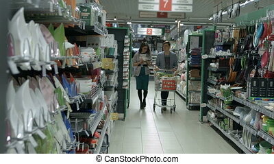 A young couple goes shopping - Girl and guy walking through...