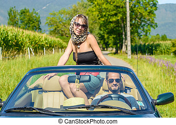 a young couple in a convertible car