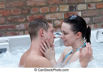 A young couple in a jacuzzi