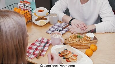 A young couple in cafe talking while the lunch