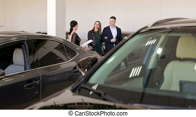 A young couple in love buys a car in the showroom, they consult with the seller.