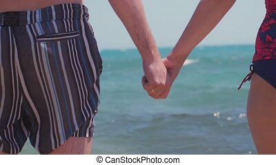 A young couple in love holding hands on the beach by the sea and splashing waves in slow motion. 1920x1080