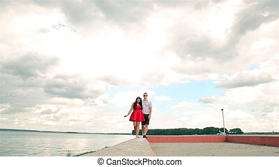 A young couple in love walking on the edge of the pier holding hands