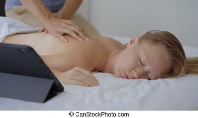 A young couple in the bedroom. Man learns how to perform a body massage for a woman by watching an online education video on a tablet. Online education concept. They stay at home because of the Covid-19 outbreak. The second wave of COVID pandemics.