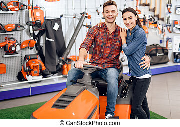 A young couple is sitting on a lawn mower. They came to the...