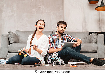 ab27e7ed62 A young couple is sitting on the floor in the living room. They collect  robots