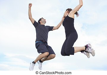 A young couple jumping on the meadow