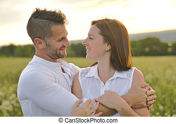 young couple kissing on the background of a sunset in the field