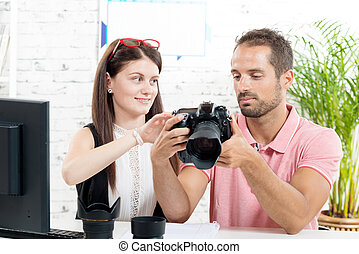 a young couple looking at pictures on camera