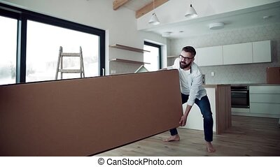 A young couple moving in new home, carrying a large box. Slow motion.