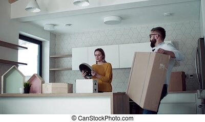 A young couple moving in new home, talking.