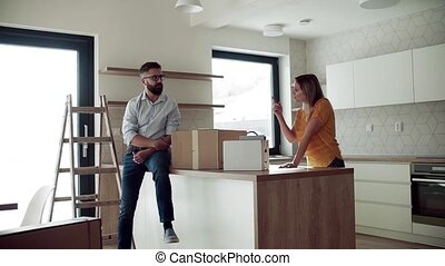 A young couple moving in new home, talking. Slow motion.