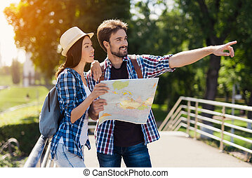 A young couple of tourists standing in the park and holding a map. They think where to go next.