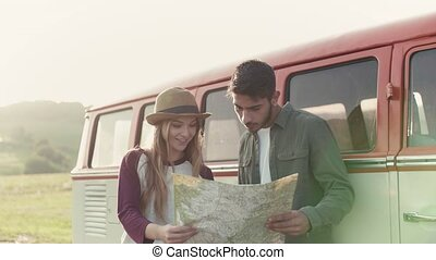 A young couple on a roadtrip through countryside, looking at...