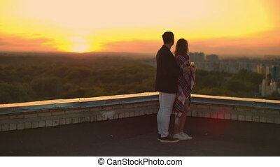 A young couple on the roof drinking wine from glasses ...