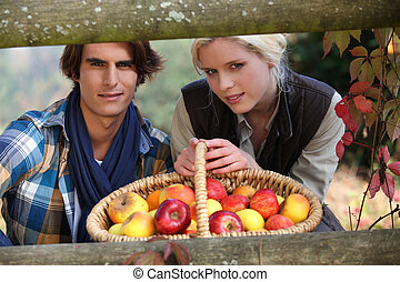 a young couple posing behind a wooden barrier with a wickerwork basket full of apples