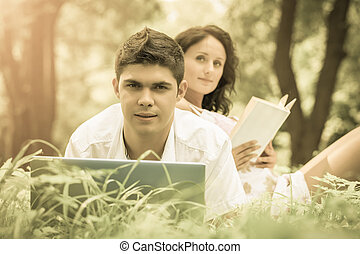 a young couple relaxing in park on green grass