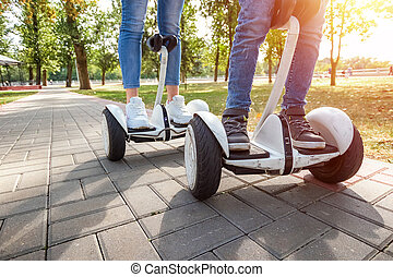 A young couple riding a hoverboard in a park, self-balancing scooter. Active lifestyle technology future