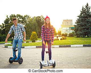 A young couple riding hoverboard - electrical scooter, personal eco transport, gyro scooter, smart balance wheel