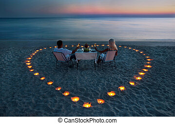 A young couple share a romantic dinner on the beach - A ...