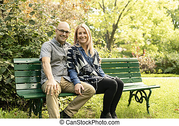 A Young couple sitting on bench at the park.