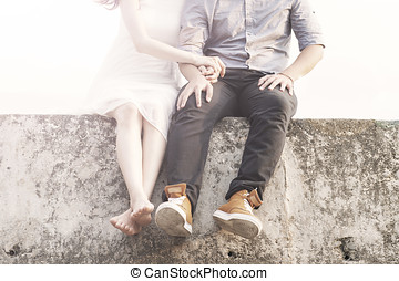 A young couple sitting on the beach